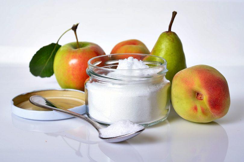 Algumas frutas, um pote de açúcar e  uma colher com açúcar