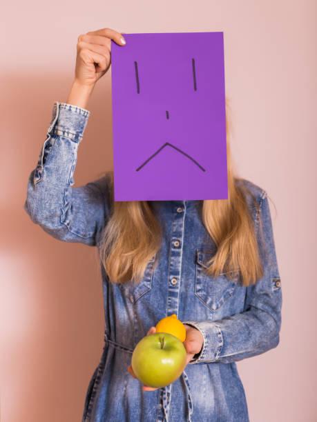 Mulher segurando frutas e um cartaz com cara triste
